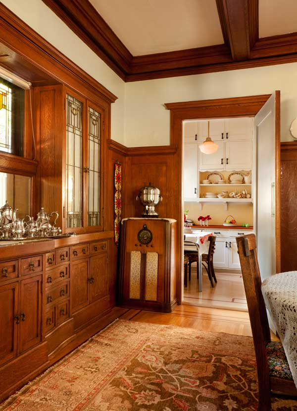 Beyond the kitchen's breakfast nook is the dining room, with its beautiful white-oak cabinets and leaded glass. The cabinet radio is vintage.