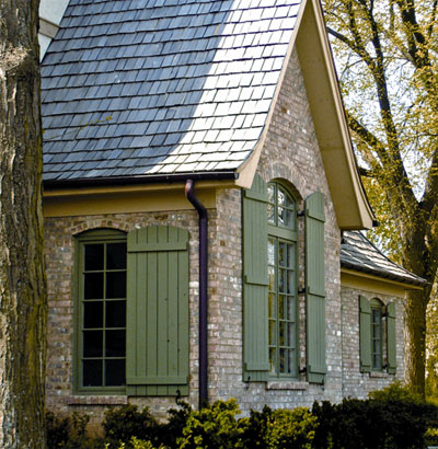Board-and-batten shutters give a house a picturesque look. (Photo: Designer Doors)