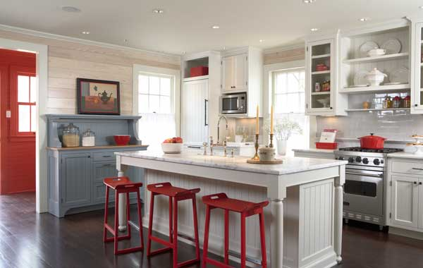 Board walls, inset cabinets, beadboard accents, and freestanding kitchen furniture are historical details in the old house. Carrara marble countertops and subway-tile backsplash are practical and timeless.