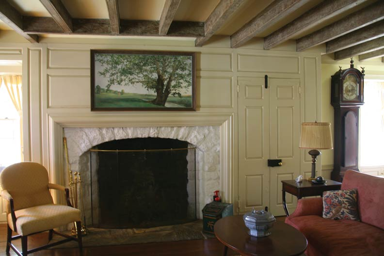 Located in a new wing of the house, the living room at Hillendale replicates typical details used in the early 18th century, like a paneled fireplace wall and exposed ceiling beams.