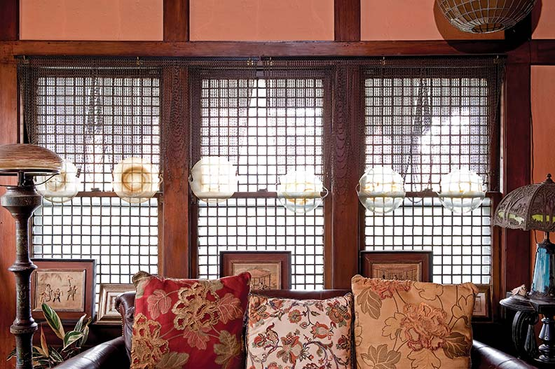 Lamps of the early 20th century flank a sofa piled with pillows; blown-glass globes suspended on chains are used in lieu of curtains, complementing the Far Eastern aesthetic.