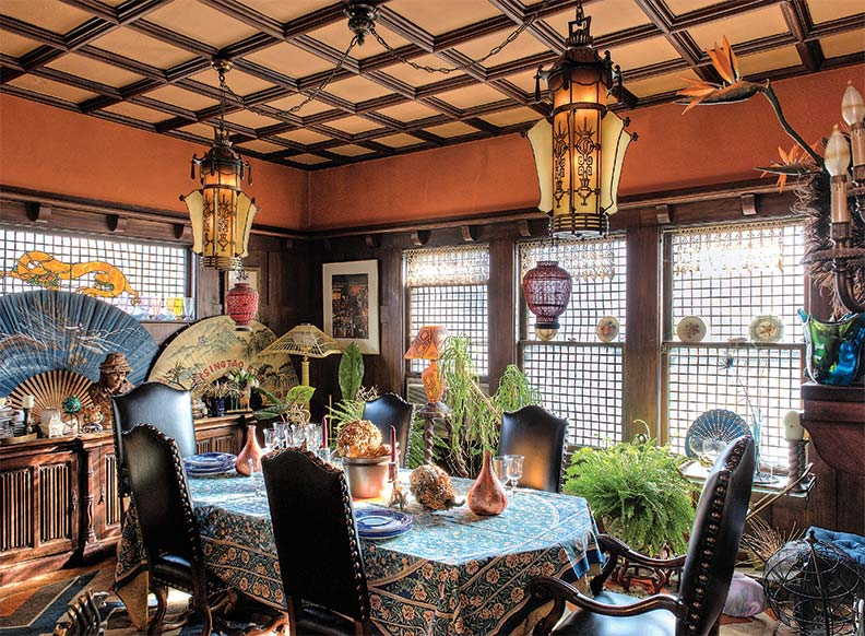 A pair of salvaged Chinoiserie chandeliers lights the dining room, which retains original stained and leaded glass windows and teak woodwork.