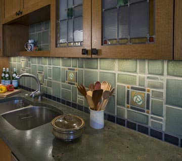 For this project, artisans at Buddy Rhodes made concrete in custom colors of moss- and slate-green, inset with veins of sand and coal, to complement earthy Motawi tiles.