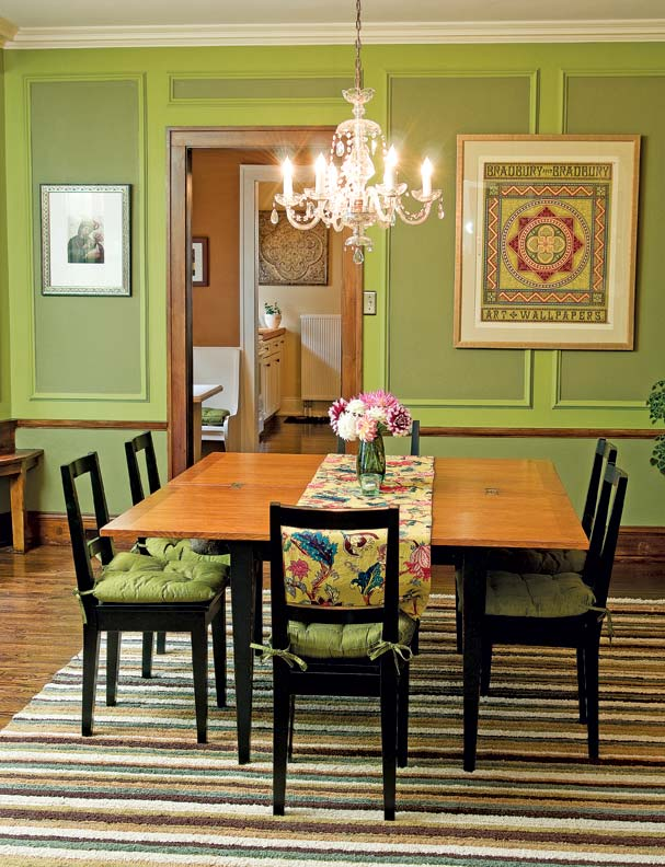 The dining room's Italian-villa red and avocado green were early colors found on the original plaster. Chris reinstalled a plate rail and wainscoting by following ghosted outlines on the wall; he also replaced columns.