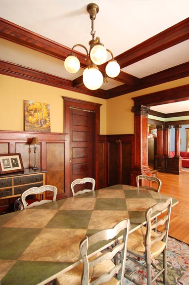 he 180-degree swinging door linking the kitchen and the dining room is new, created from a five-panel door repurposed from elsewhere in the house and carefully inserted into the existing wainscoting.