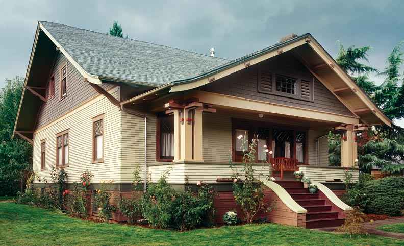 Decorative flared columns support the gabled front porch, complete with exaggerated soffit overhang.