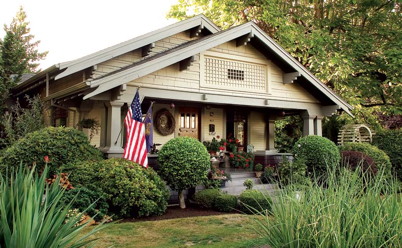 A multitude of Arts & Crafts details, such as a gable lattice and tapered columns, help layer this inviting front-entry façade.