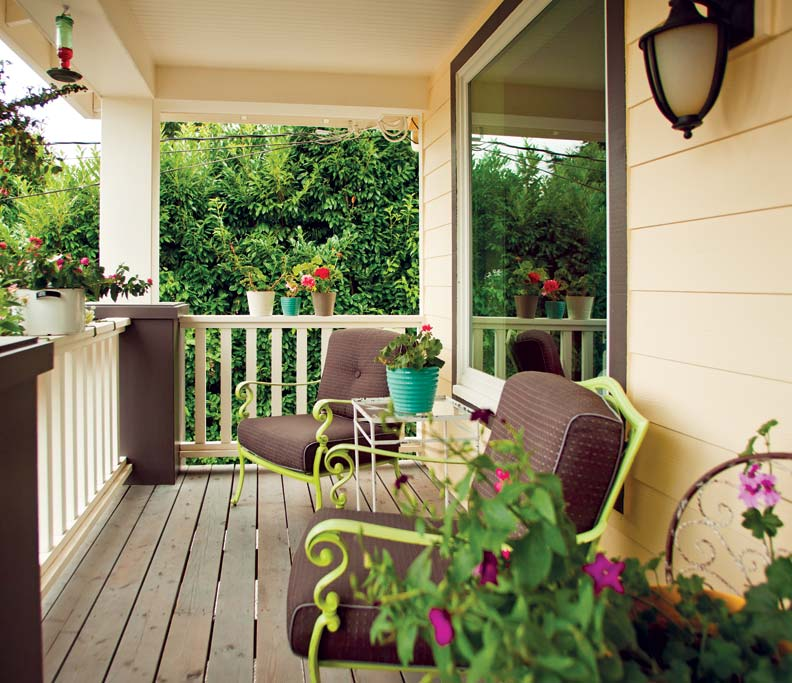 Cased Beams And Simple Railings Help To Frame A Front Porch Sitting Area While An