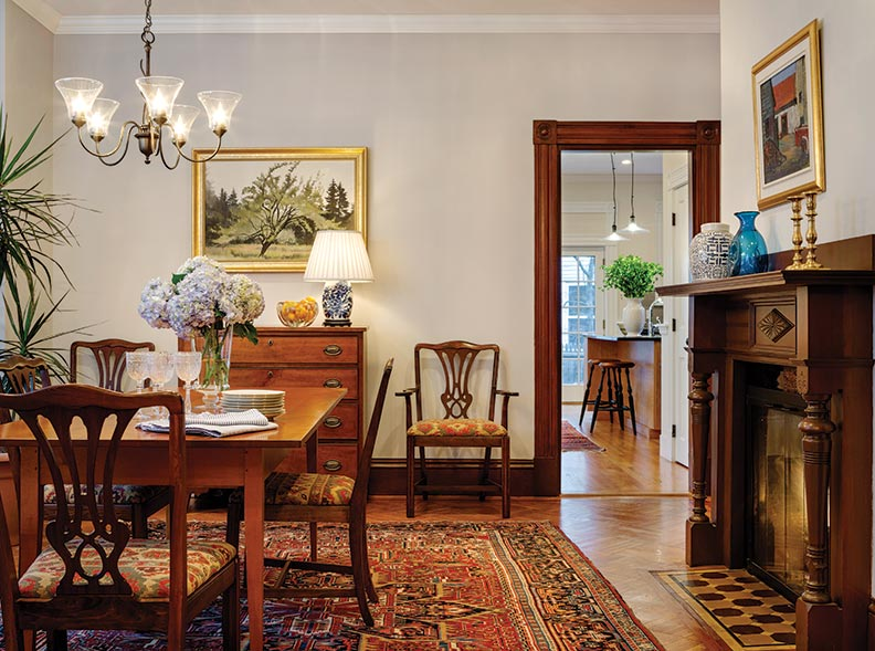The dining room has early 19th-century furniture, reproduction light fixtures, and vintage oriental rugs. Fireplace tiles and parquet flooring were still there, under other materials.
