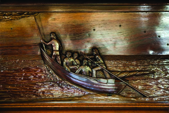 Bogdahn carves the Nantucket sleigh ride into a mantelpiece.