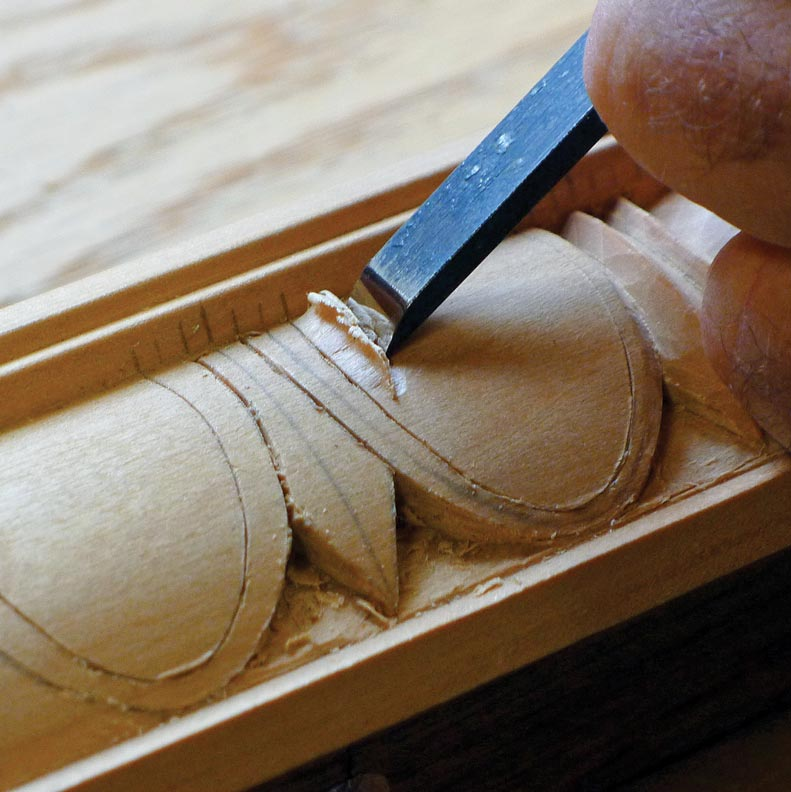 Cutting out the egg-and-dart pattern with a chisel