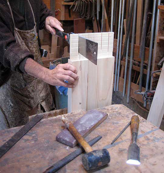 Charles Prowell cuts the kerfs for the bubinga wedges.