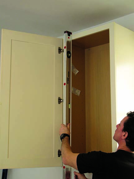 install kitchen cabinets Check upper cabinets for plumb