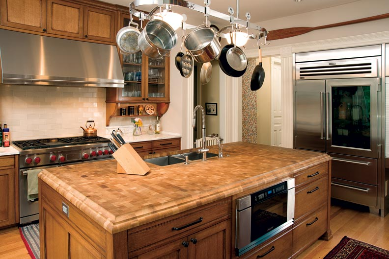 The kitchen's center island is softened by a butcher block top with profiled edges.