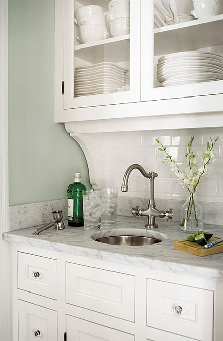 Just off the kitchen, a small dish pantry has marble countertops and a subway tile backsplash.