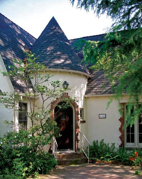 A distinctive feature in Norman-style houses is a semicircular, conical-roofed entry between two wings of the house. This fine example has an arched entry trimmed in red brick.