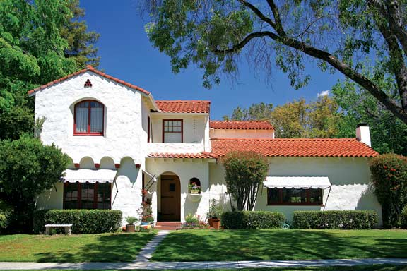 Designed by Lena Robbins in 1927, this Spanish Colonial Revival house has been handsomely restored with traditional Spanish-style awnings, and features a combination of one- and two-story wings and a projecting second floor set atop small arches.
