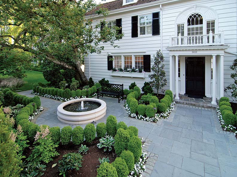 An understated fountain echoes the home's classical lines.