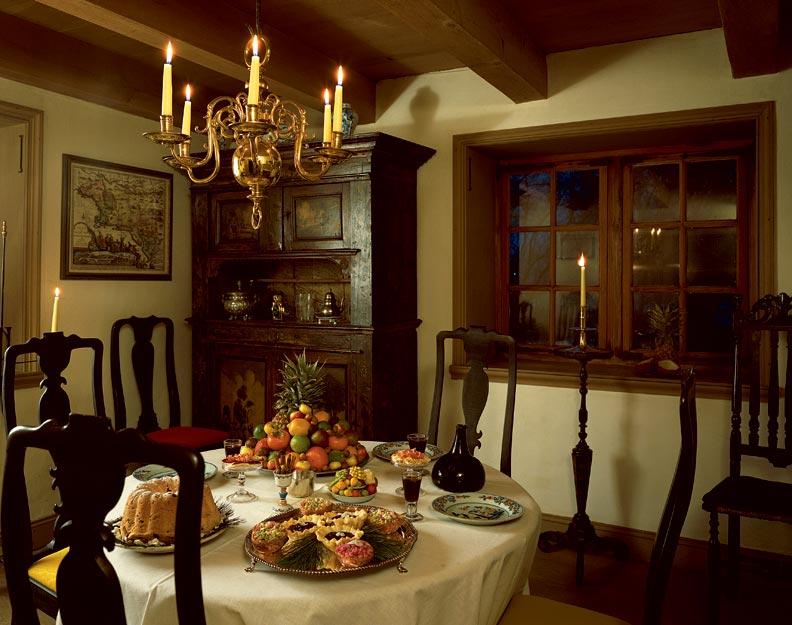 An ornate brass chandelier with candles in an 18th-century room is the early American ideal.