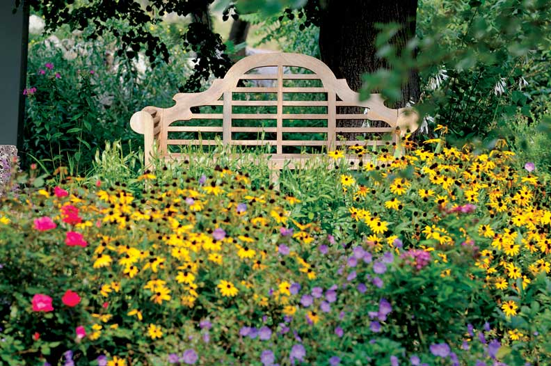 The slight setback of most Colonial homes presents a challenge in garden design, but bright perennials make the most of this space.