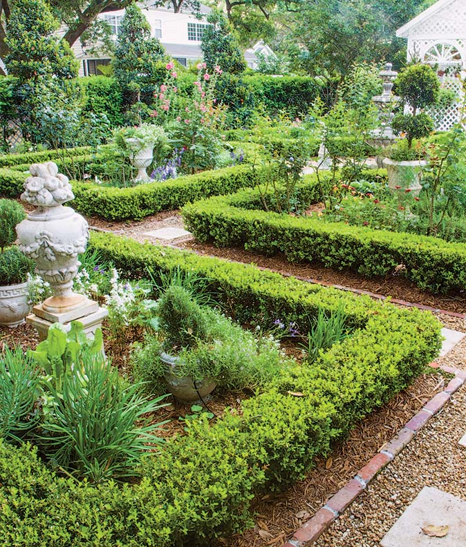 Boxwood outlines beds in a geometric arrangement featuring urns and statuary.