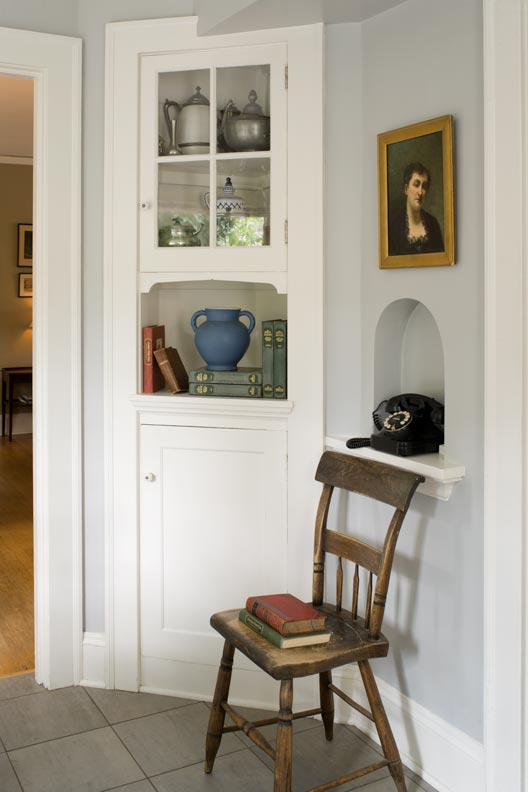 This painted corner cabinet, original to the breakfast room, inspired the straightforward design of the paneled kitchen cabinets. They replaced the dark particle-board units of a floral orange 1970s remodeling.
