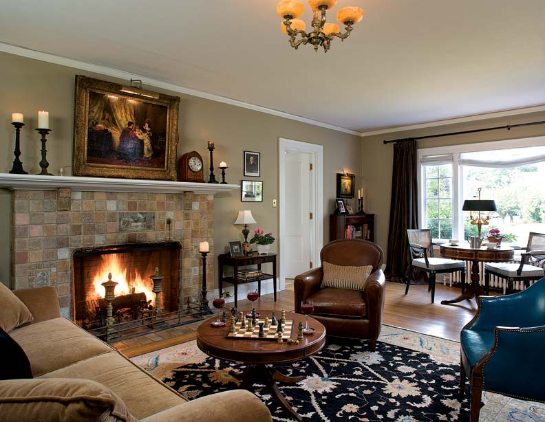 """Soft neutrals in the original Batchelder tiles suggested a """"light coffee"""" color for living-room walls. Brass andirons warm the browns. Leather club chairs join an English-style rolled-arm sofa. A 19th-century oil hangs over the fireplace."""