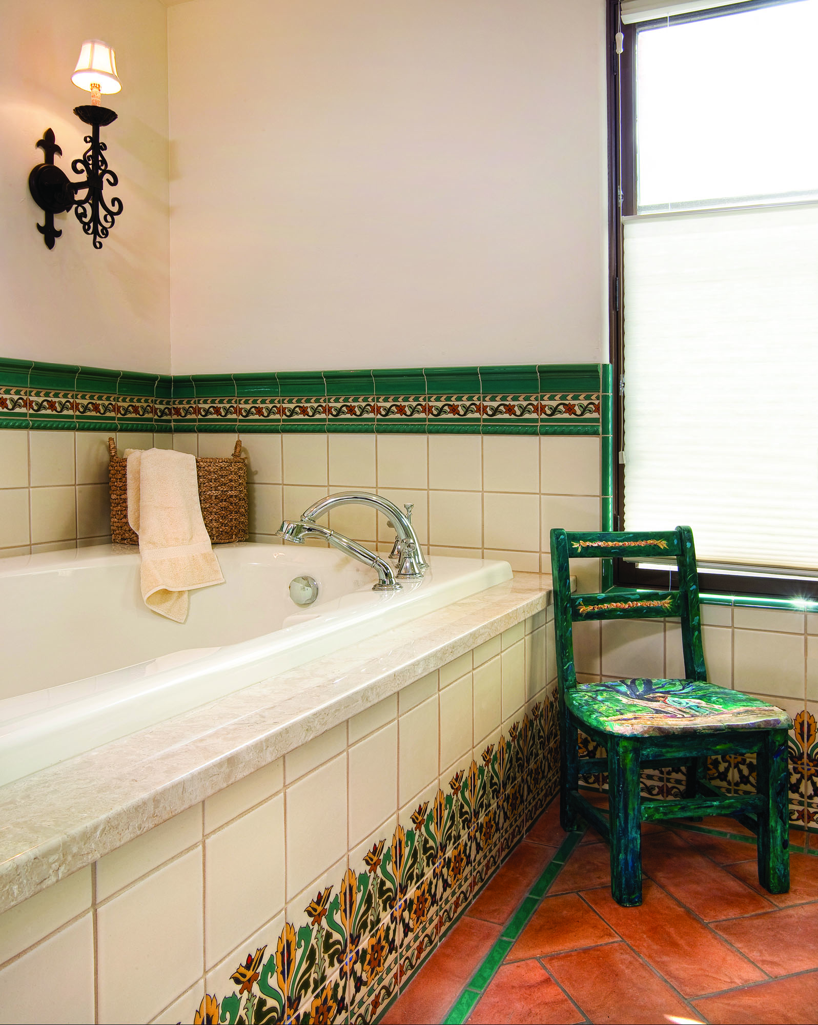 In the master bath, located in space that used to be the master bedroom, both the green backsplash and cap tiles, and the exotic design at the base of walls, are contemporary reproductions of California tile.