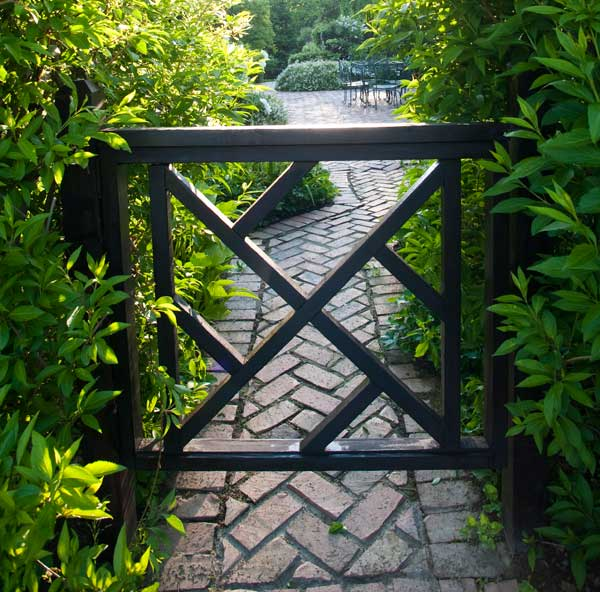 Coming from the meadow, the Chippendale-style gate looks into the courtyard and its herb garden.