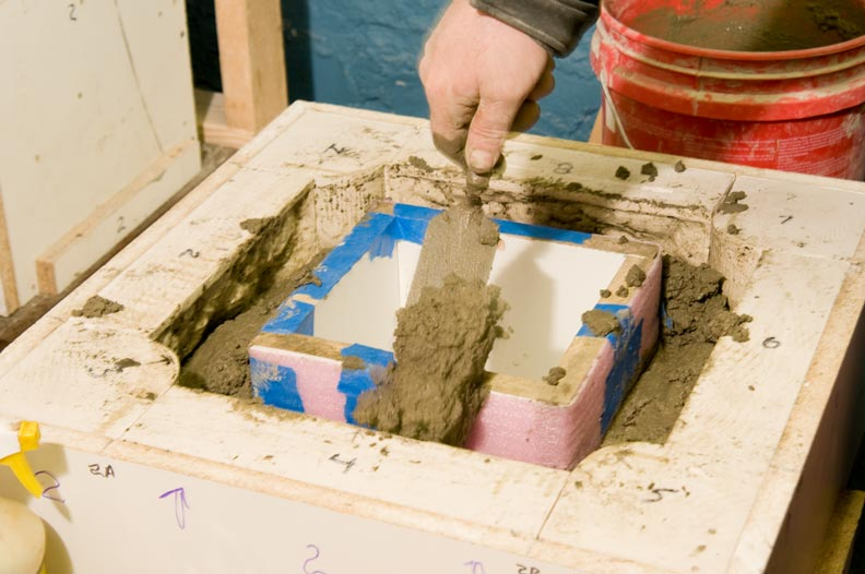 Marty fills around the form with concrete, adding rebar for strength at mid-fill, and finishing by vibrating the interior block to spread the concrete.