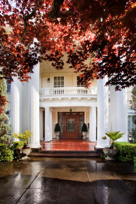 Corinthian and Doric columns lead the eye toward the main entrance and a stunning mahogany door with original art glass in an Art Nouveau style.