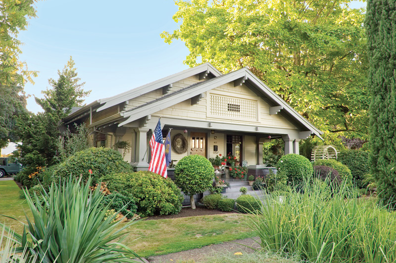 A subdued paint scheme brings out the architecture of this 1915 Craftsman Bungalow, while planted containers and a flag add pops of color.
