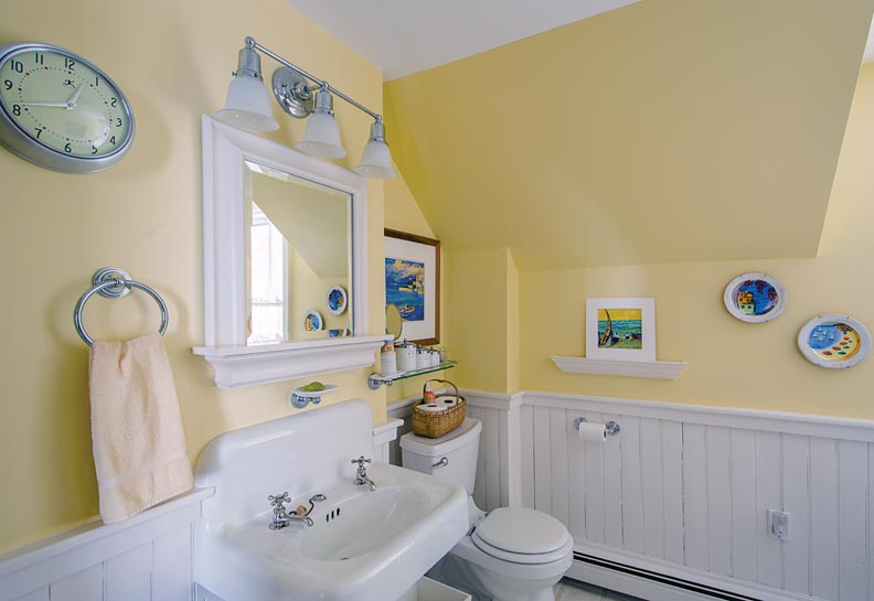 Beadboard wainscoting and simple fixtures define the cottage bath.