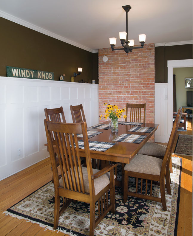 The dining room sports high wainscoting and the home's original Windy Knob Orchards sign.