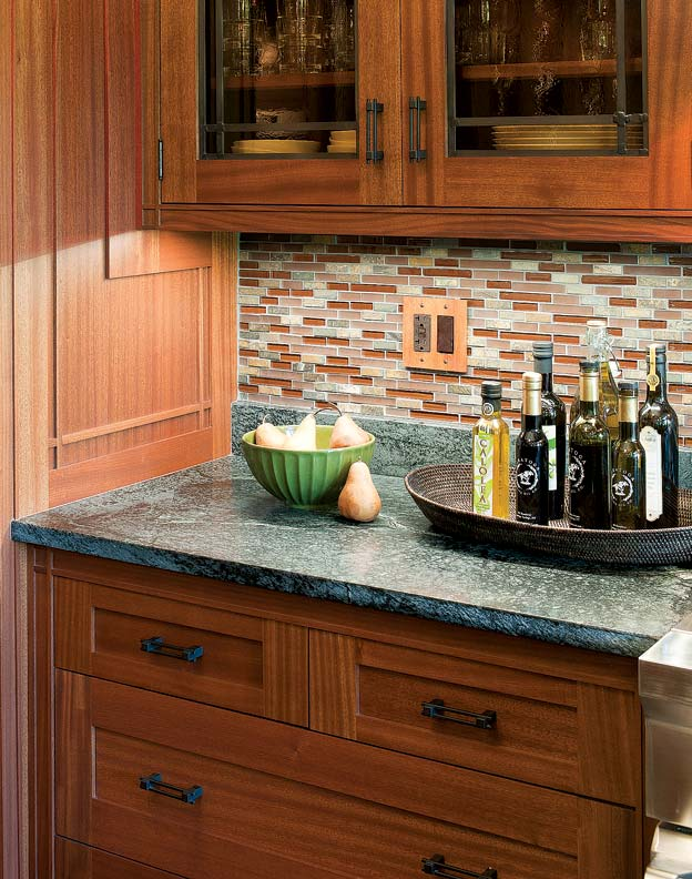 The tile backsplash offers warmth and interest in the design; cabinet doors are made of leaded glass.