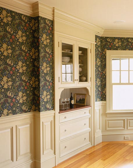 Custom raised-panel millwork in creamy white is a new addition to a Colonial Revival-era house.