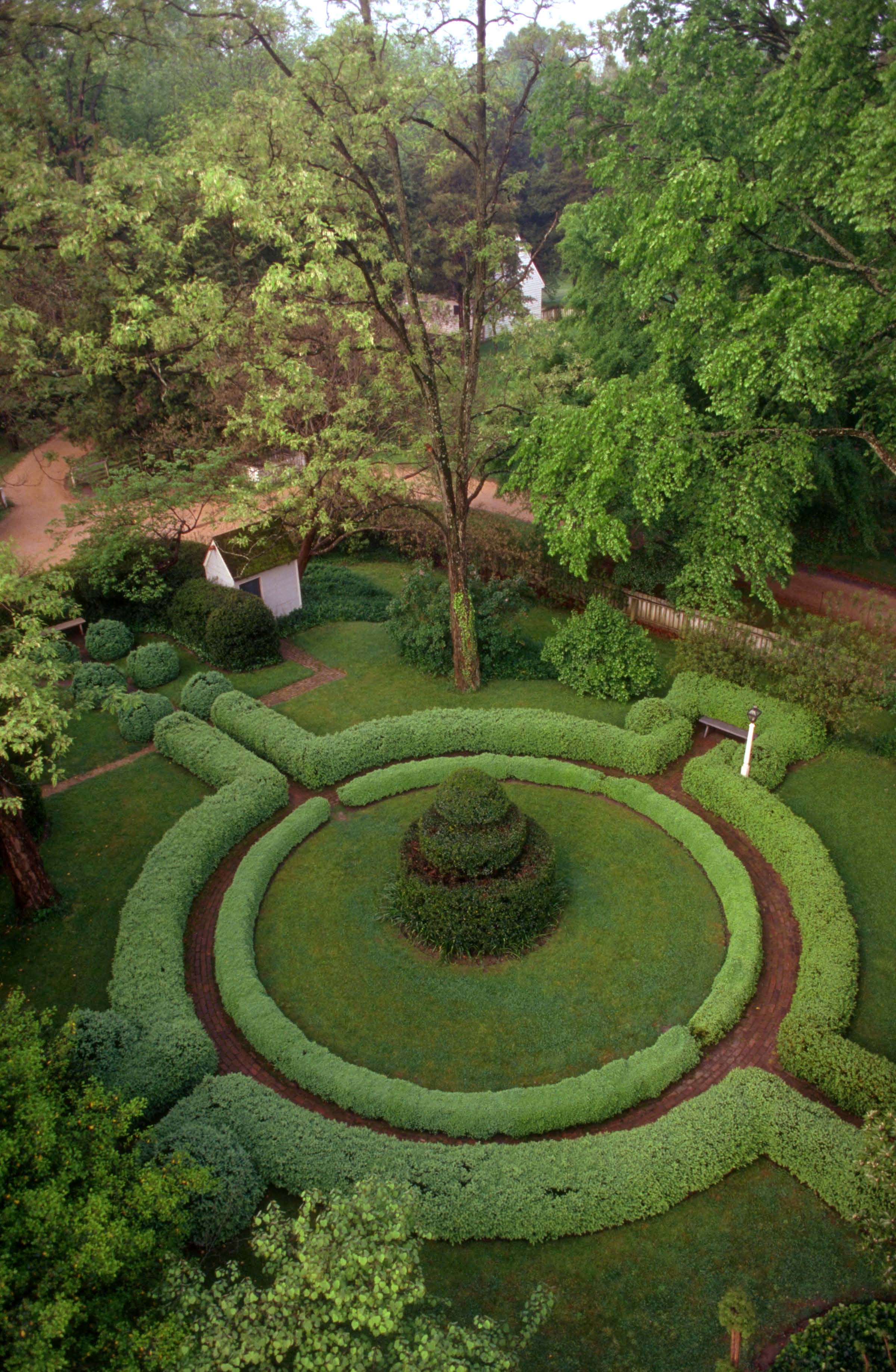 At the center of the Colonial Revival Greenhow-Repiton garden, a spiral topiary centers a circle around which lawns and beds radiate.