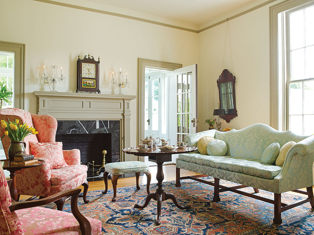 Antiques and custom upholstered furniture are formally arranged in the east living room. The pillar-and-scroll clock, ca. 1815, is still marking time.
