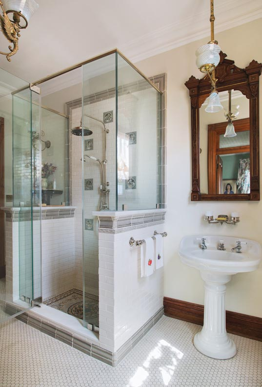 A pedestal sink and hex floor tile add an old look to the second-floor bath.
