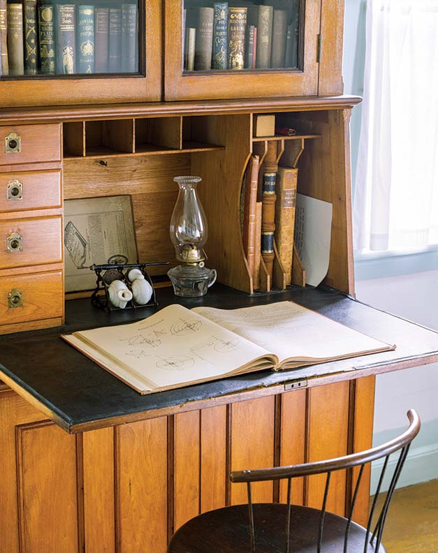 A rather plain secretary of the mid-19th century provides cubbies.