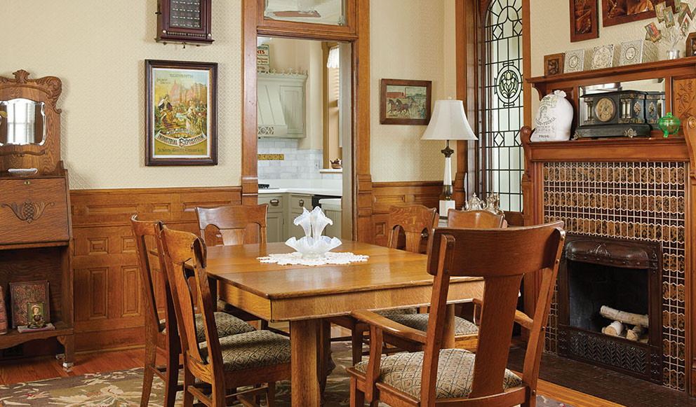 The low oak wainscot and preponderance of windows lends a sweetness unusual for Victorian dining rooms. The leaded glass pair is from salvaged 19th-century French doors.