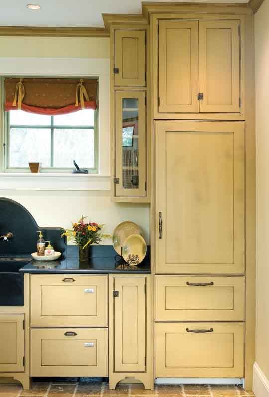 Dishwasher drawers, refrigerator, and freezer are integrated into the buttermilk-colored cabinets.