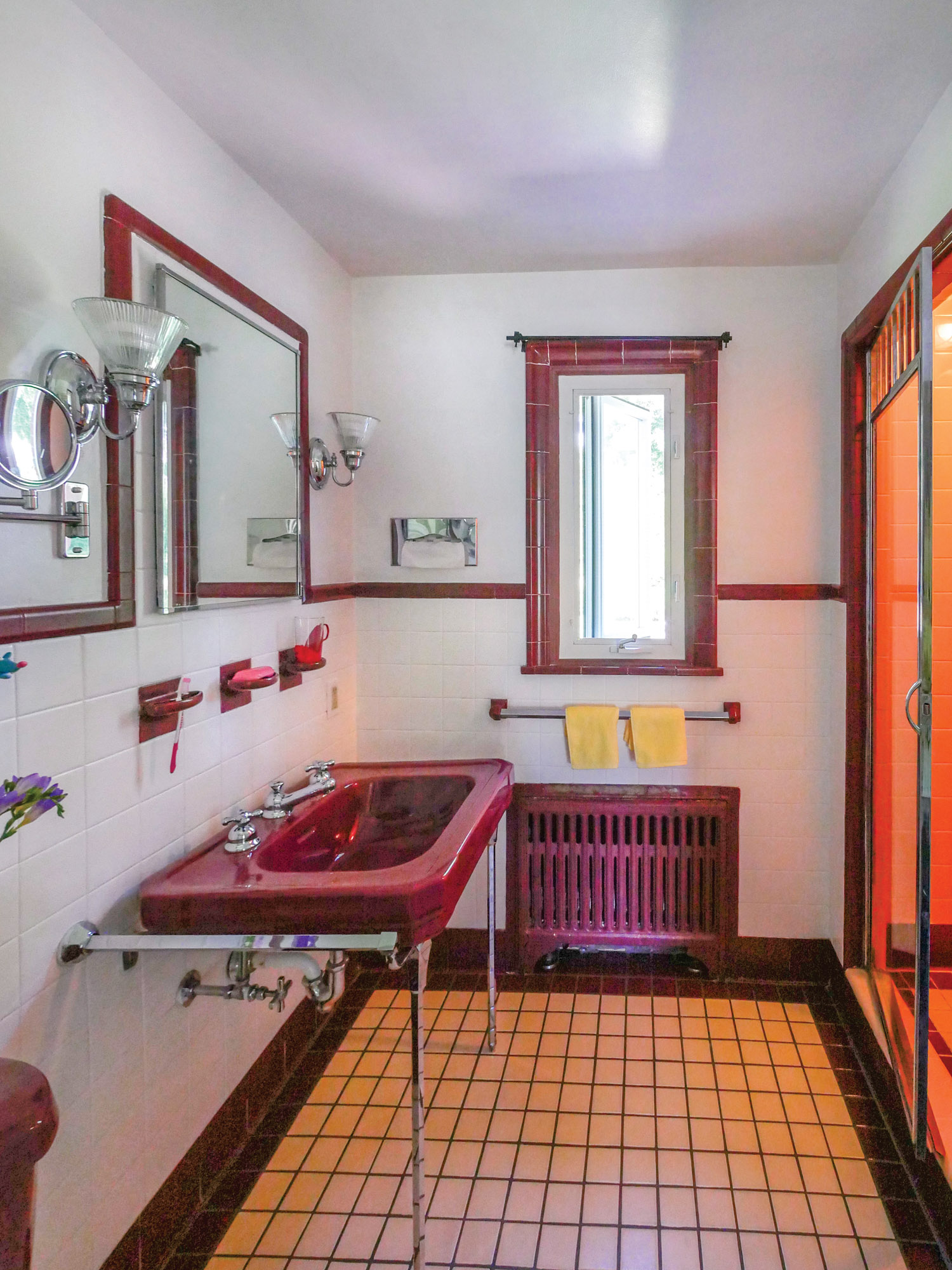 Similar to the blue and white bath, a third bathroom has burgundy accent tile and fixtures.