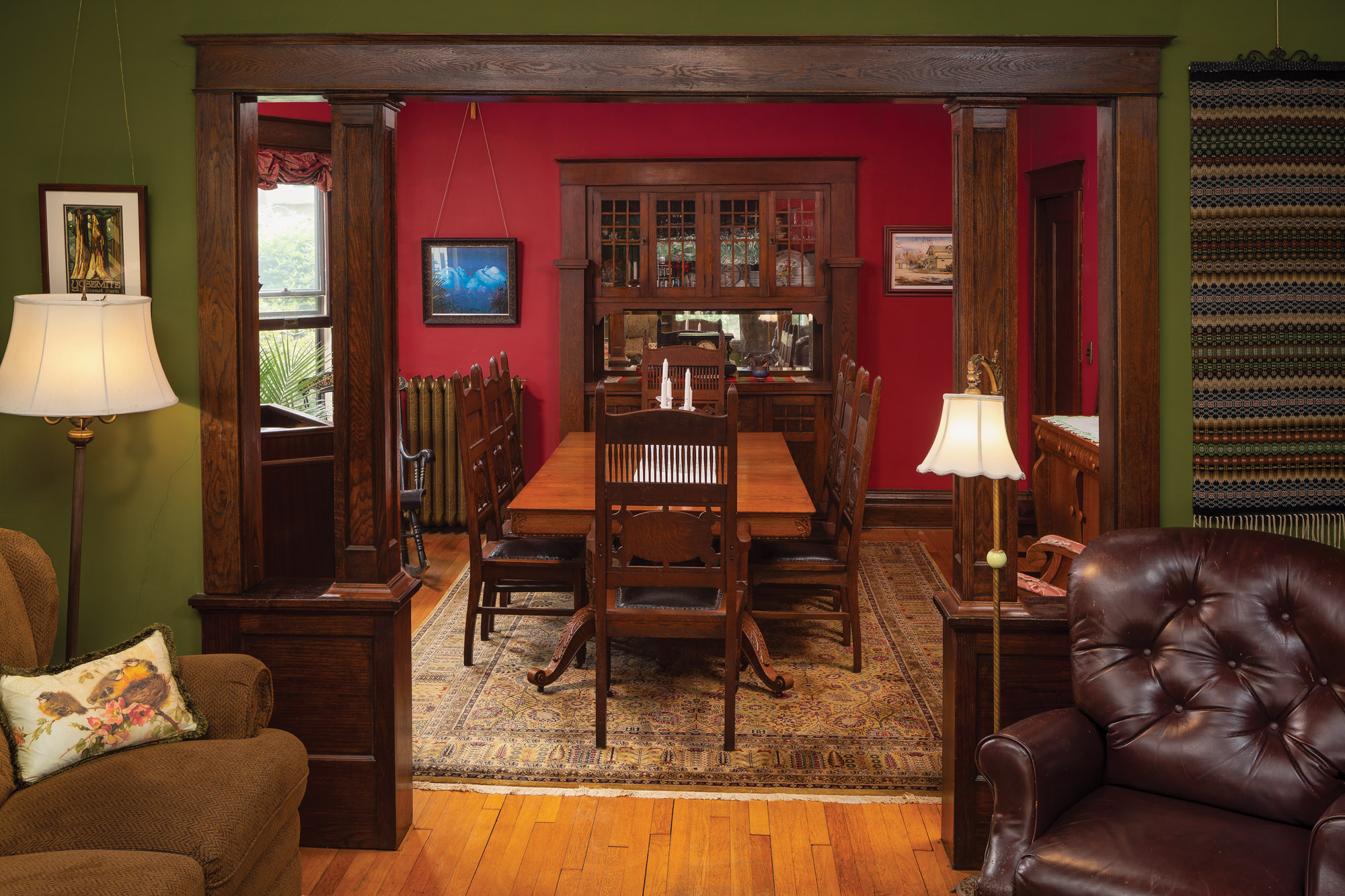 The Erstads found a carved dining table that can seat 12, and nine matching chairs: They bought six of the chairs at an auction, and, a few days later, discovered three identical chairs in a shop. The room has its original built-in buffet; the swinging door opens to the kitchen.