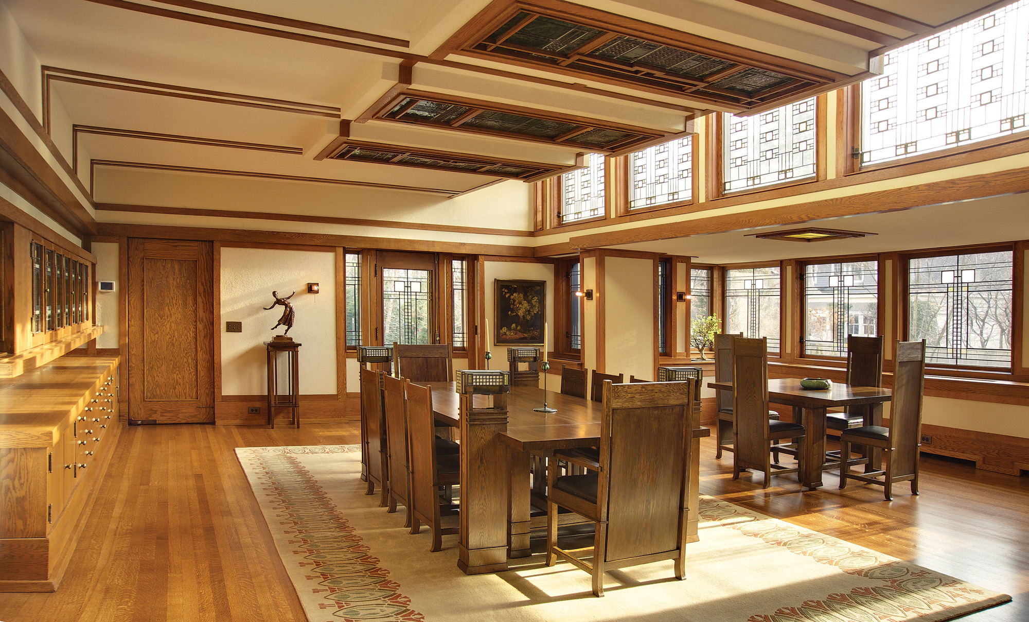 The dining room is the focal point of the home. Leaded windows and art glass in the doors of the built-in server took 3,000 pieces of glass. The Wright-designed tables and chairs remain in the space he designed 109 years ago.