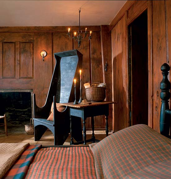 More illumination is provided in this bedroom than would have been the case in 1700, but nothing looks overdone: candles, an electrified sconce, and low-wattage bulbs.