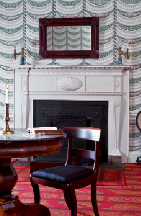A Federal mantel at a ca. 1815 Palladian house in Louisville, Kentucky, features a sunburst centerpiece and graceful tapering pilasters.