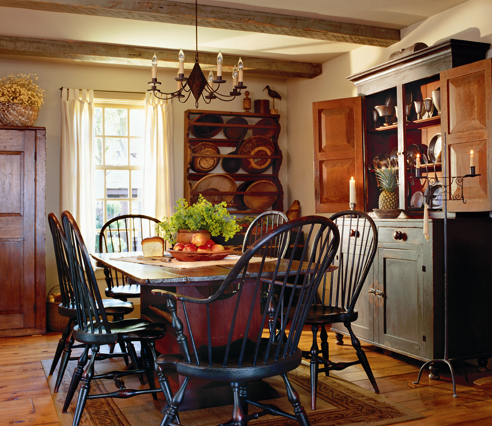 A reproduction double-cone wire chandelier complements a farmhouse dining room furnished with a mix of antiques and reproductions.