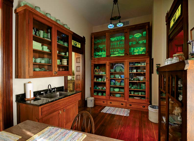 The display cabinet doors in the butler's pantry were rescued from the hayloft of the carriage house; the cabinets now house Pam's extensive collection of jadeite dishware. The table in this room was created from a marble slab discovered underneath the stove in the kitchen.