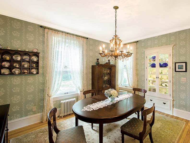 In the dining room, simple Colonial Revival and Empire style furnishings mix with soft aqua French-style wallpaper and lace panels.